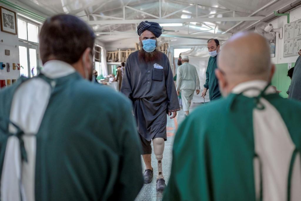 Mullah Yacoub (C), a Taliban member who claims to have lost his leg in an US strike, walks to try on his new prosthetic leg