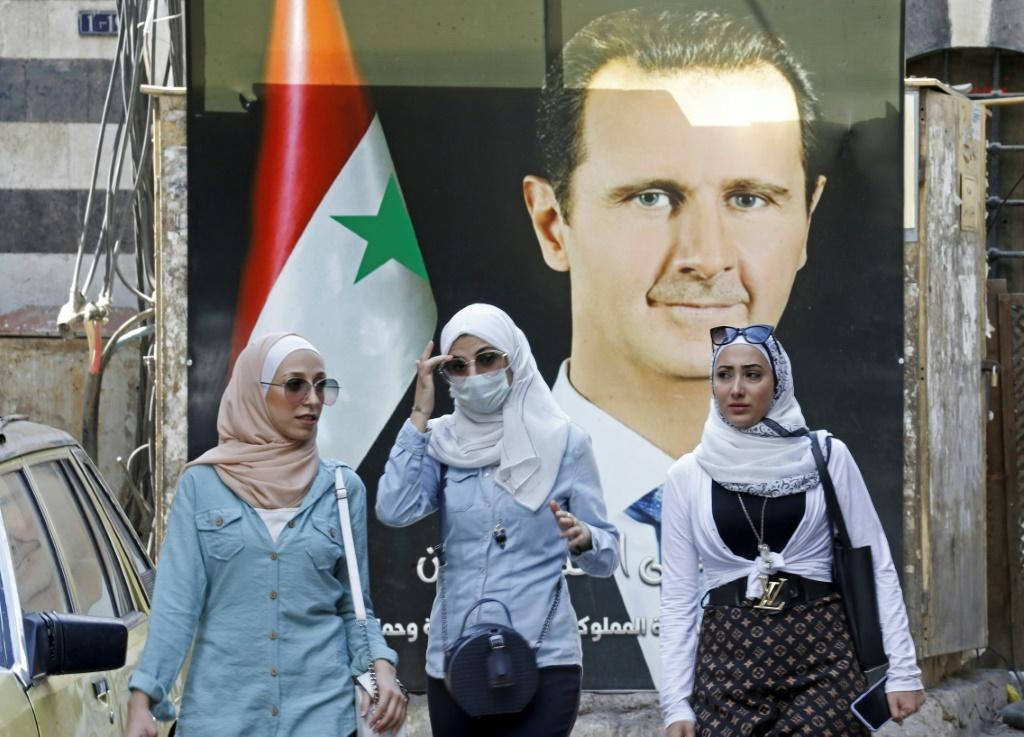 Syrians walk in front of a poster of President Bashar al-Assad near the Grand Umayyad Mosque in Damascus on September 23, 2021