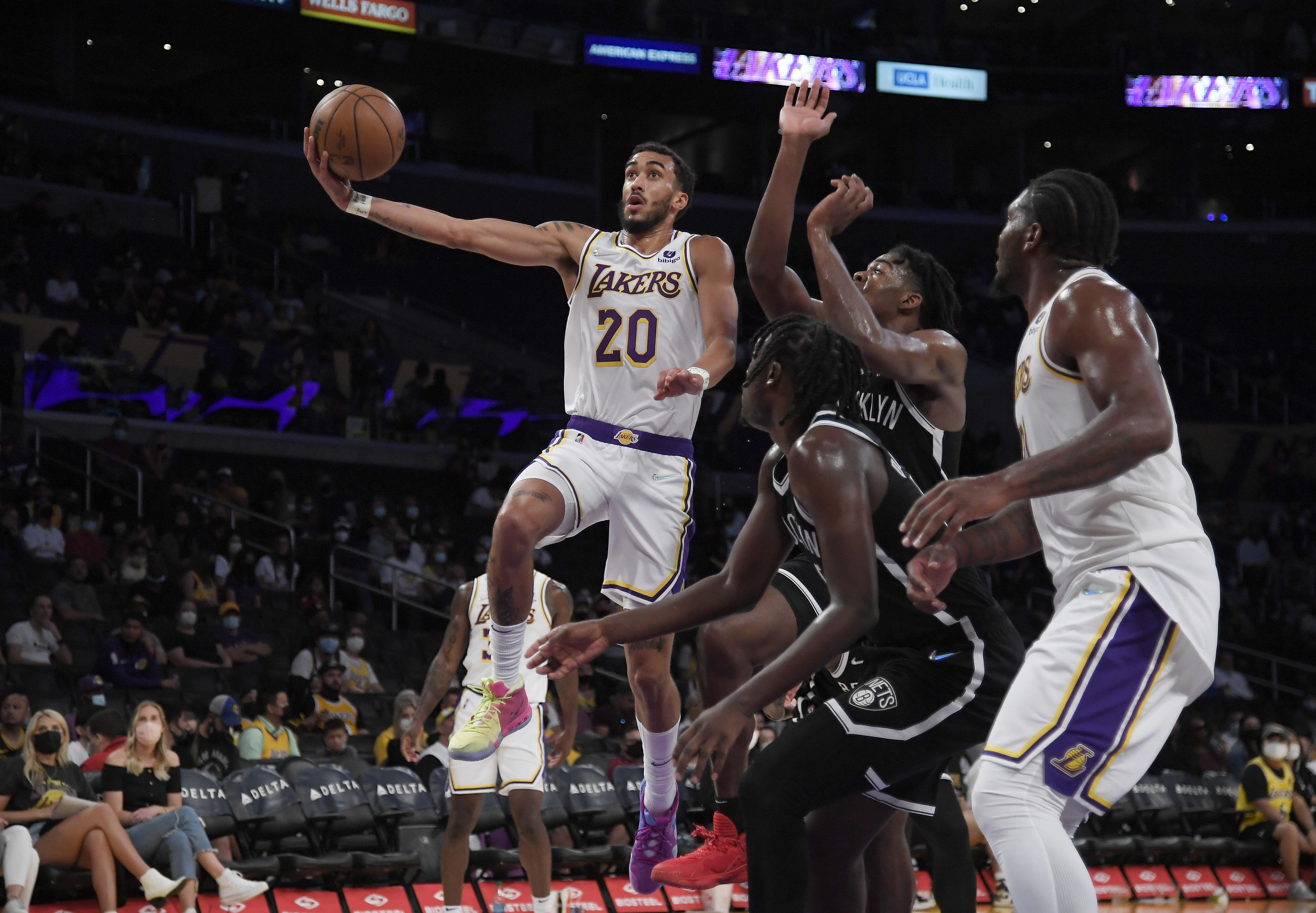 Trevelin Queen #20 of the Los Angeles Lakers goes up for a basket against Sekou Doumbouya #45 and Day'Ron Sharpe #20 of the Brooklyn Nets