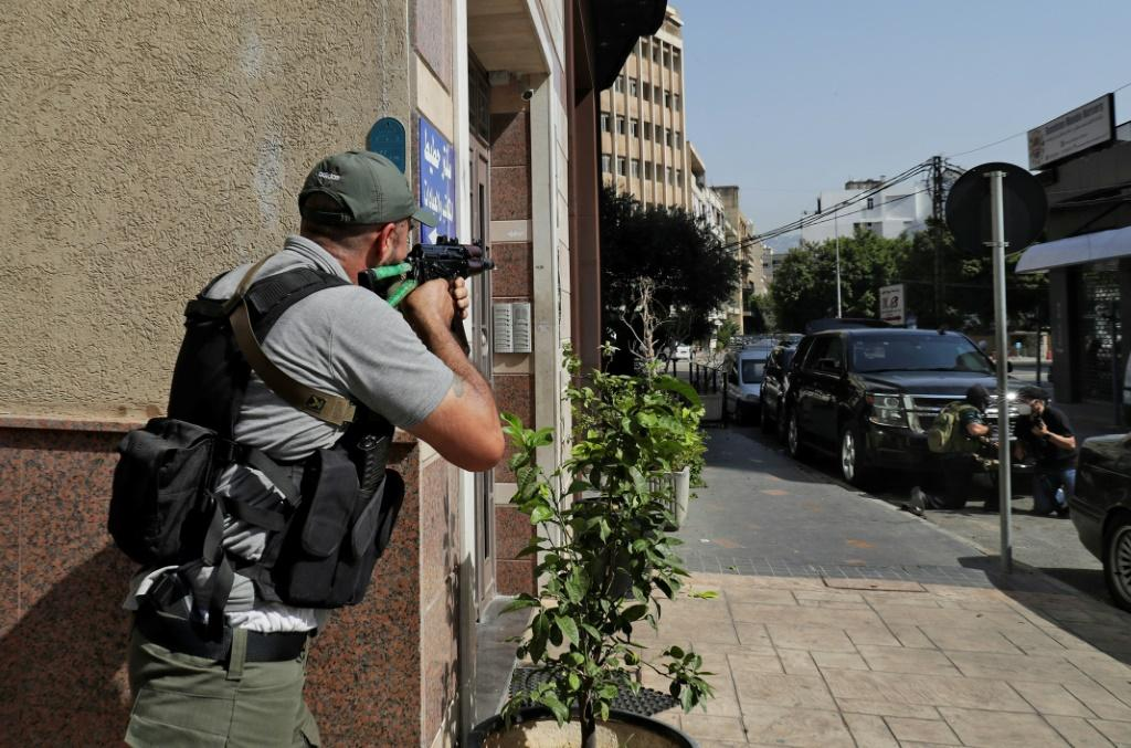 A fighter of the Shiite Amal movement takes aim during clashes in Tayouneh in Beirut's southern suburbs