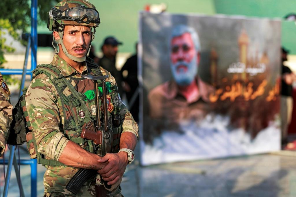 A member of Iraq's Hashed al-Shaabi (Popular Mobilisation) paramilitary forces stands guard during an election rally for the Asaib Ahl al-Haq movement in Baghdad on October 7, 2021