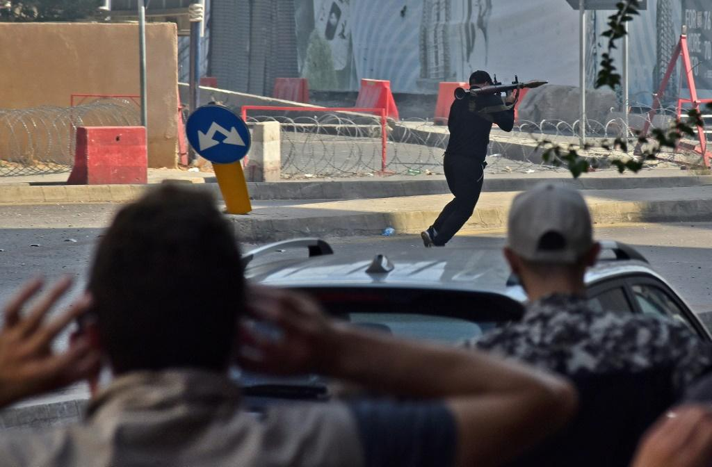 A Shiite activist armed with a rocket-propelled grenade launcher moves along a street in the Tayouneh area of Beirut