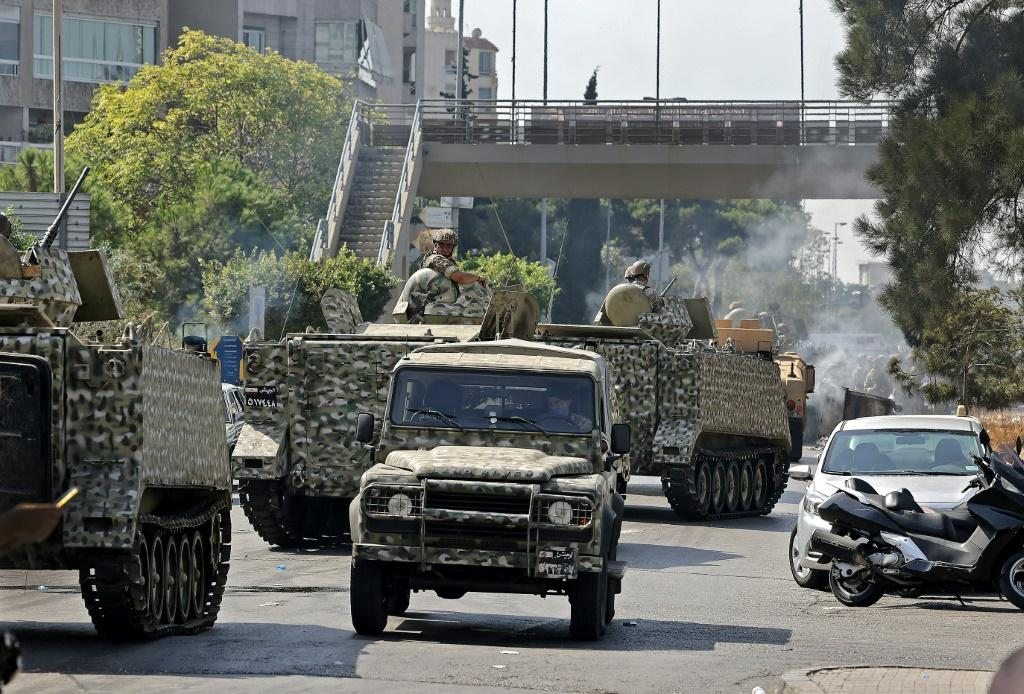 An armoured column of Lebanese troops deploys to Tayouneh, in the mainly Shiite southern suburbs of Beirut, after deadly violence erupts at a protest demanding the replacement of the lead investigator into last year's monster port blast