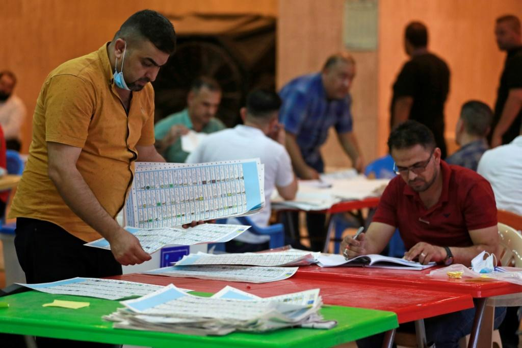 Employees of Iraq's Independent High Electoral Commission conduct a manual count of votes following the parliamentary elections in Baghdad's Green Zone area on October 13, 2021