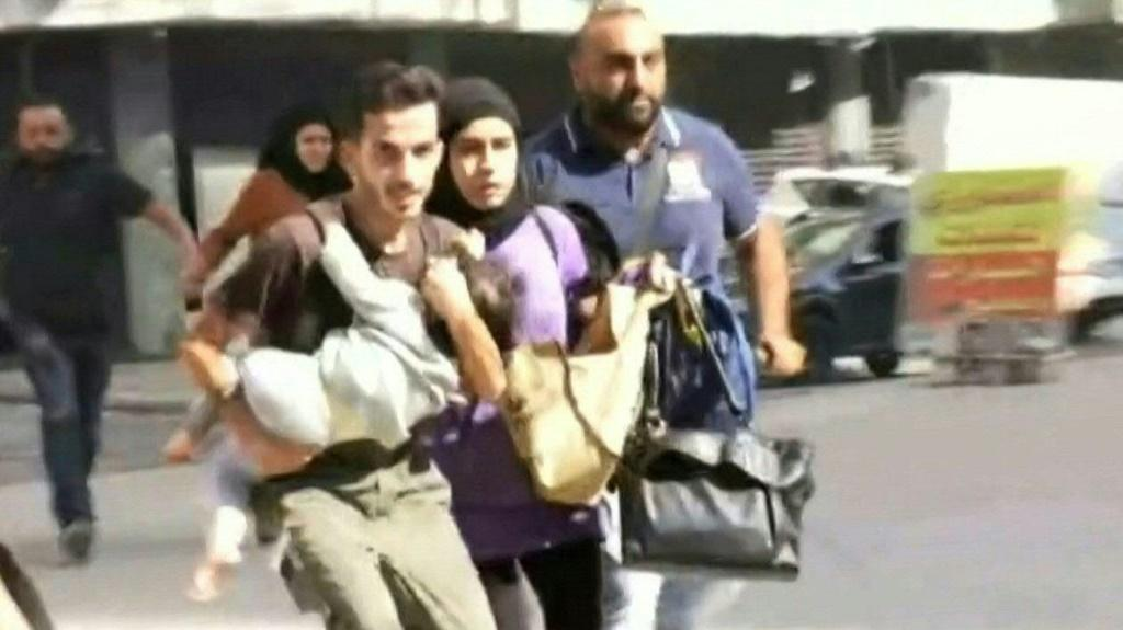 IMAGES A family runs holding their child as they flee the Tayouneh neighbourhood of Beirut during intensive gunfire clashes that broke out following a Beirut rally organised by the Shiite Hezbollah and Amal movements to demand the dismissal of the lead i