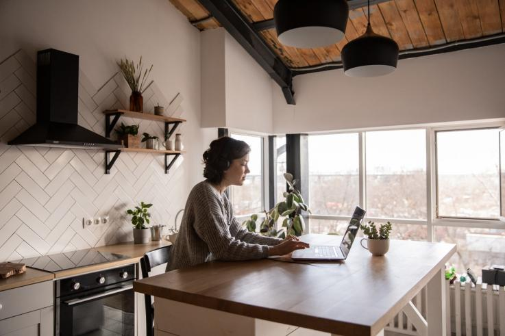 young-woman-surfing-laptop-in-kitchen-4049990