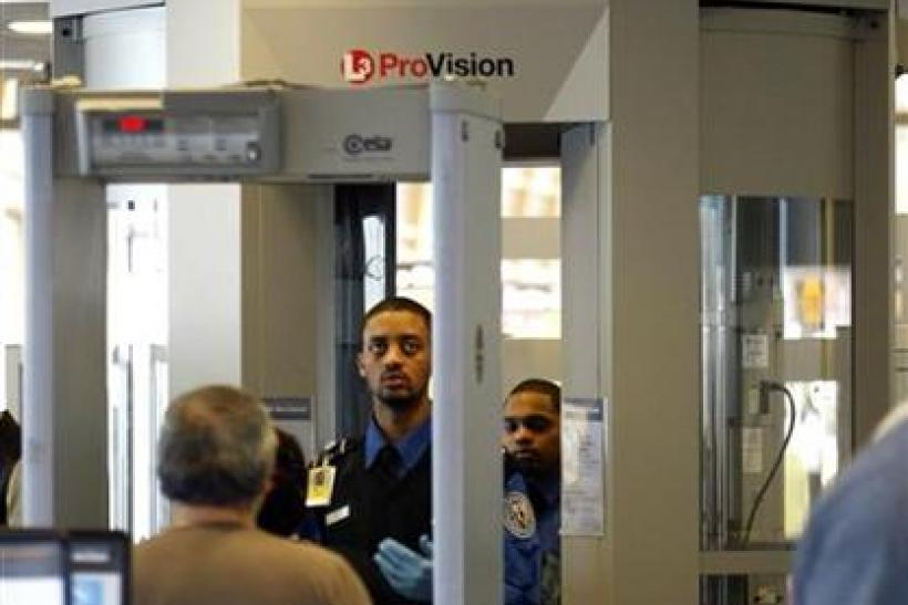 A TSA worker stands in front of a full-body scanner as he directs passengers at the departure security line at Reagan National Airport in Washington