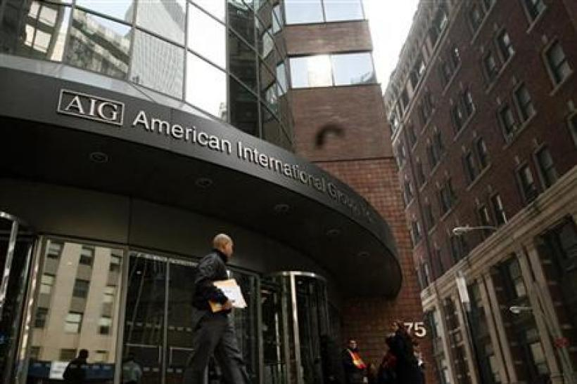 A man walks past the American International Group (AIG) building in New York's financial district