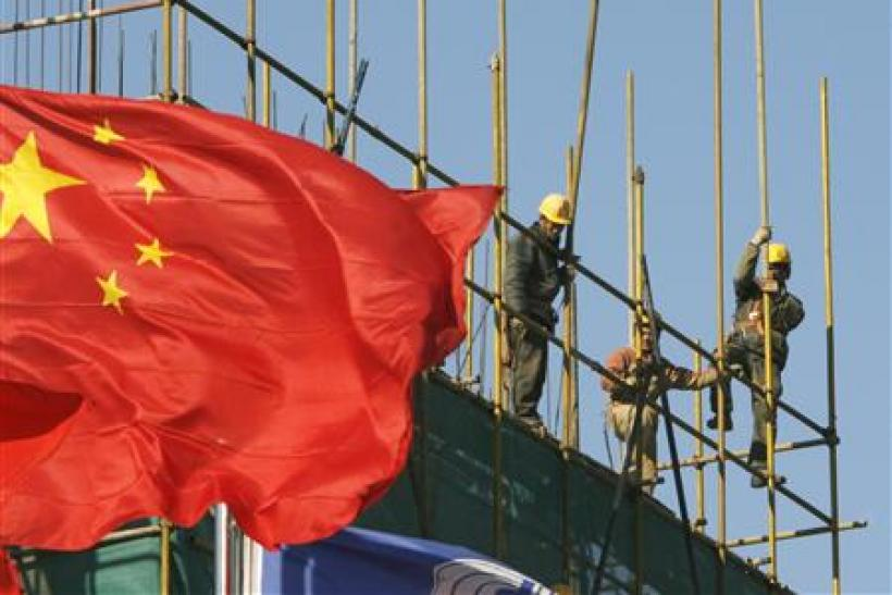 Workers install scaffolding at a construction site as a Chinese national flag flies near by in central Beijing