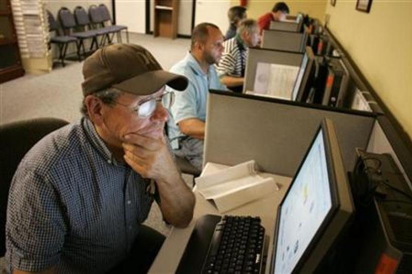 Stephen Battaglia (L) of West Palm Beach, Florida searches for jobs on a computer at Workforce Alliance in West Palm Beach