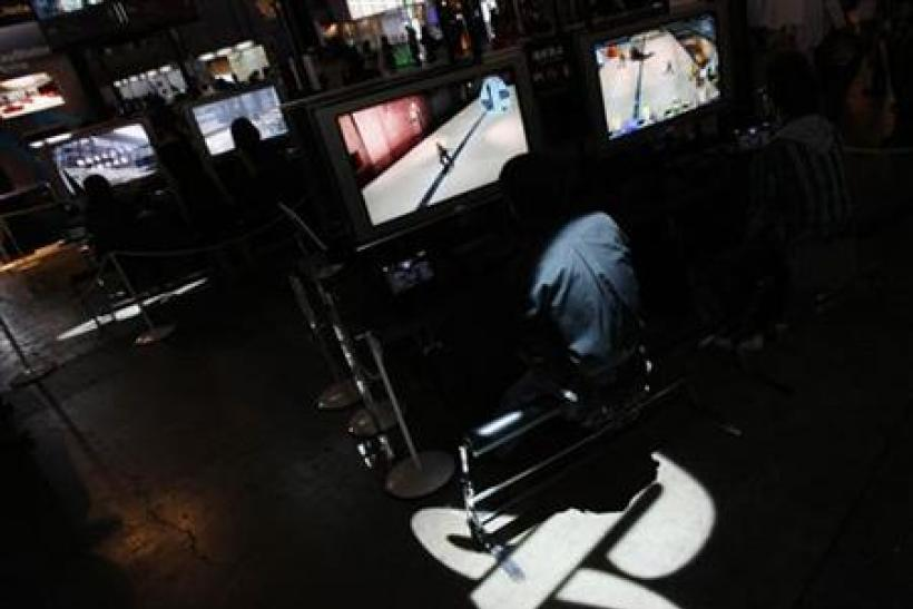 Man plays Sony's PlayStation 3 game console as logo of Sony's PlayStation displayed at the Tokyo Game Show in Chiba