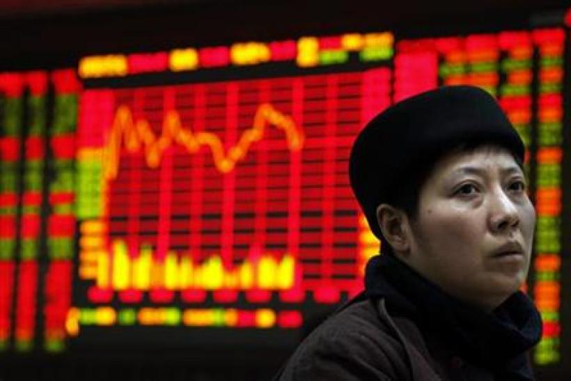 An investor sits at a terminal in front of a screen displaying stock information at a brokerage house in the financial district of Beijing