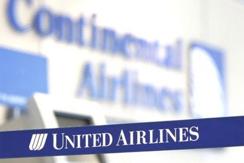 A Continental Airlines logo looms over a United Airlines logo in Chicago's O'Hare International Airport May 3, 2010
