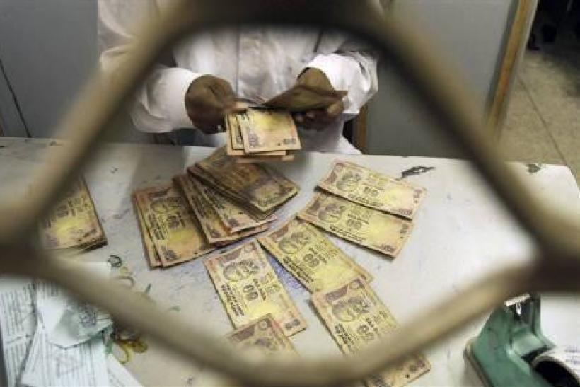 An employee sorts Indian currency notes at a cash counter inside a bank in Agartala in this February 2010 file photo.
