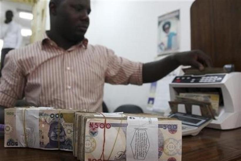 A money dealer counts the Nigerian naira on a machine