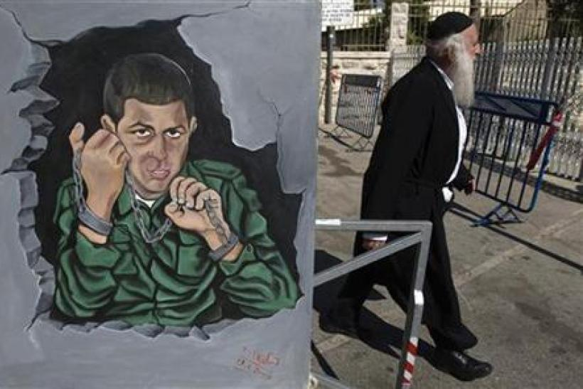 Pedestrian walks past a painting, depicting Israeli soldier Shalit, hung outside a protest tent in Jerusalem