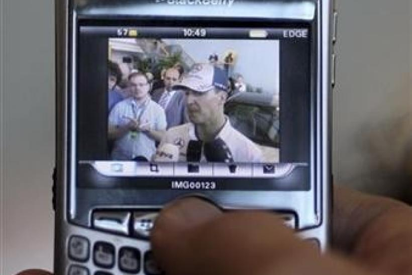 A journalist uses his Blackberry to take pictures of Mercedes Formula One driver Michael Schumacher