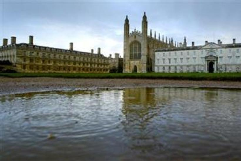 Rain drops break the surface of a puddle at the rear of Kings' College in Cambridge