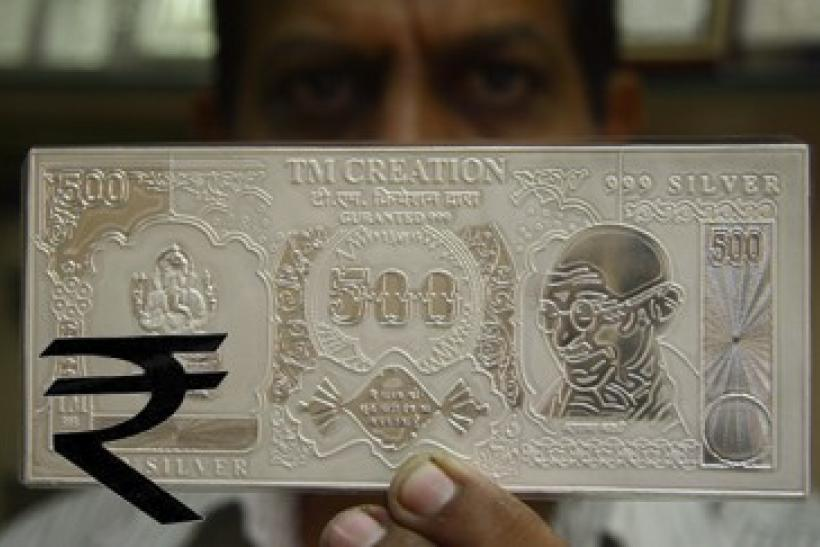 A jeweller displays a silver plate in the form of an Indian rupee note in this file photo.