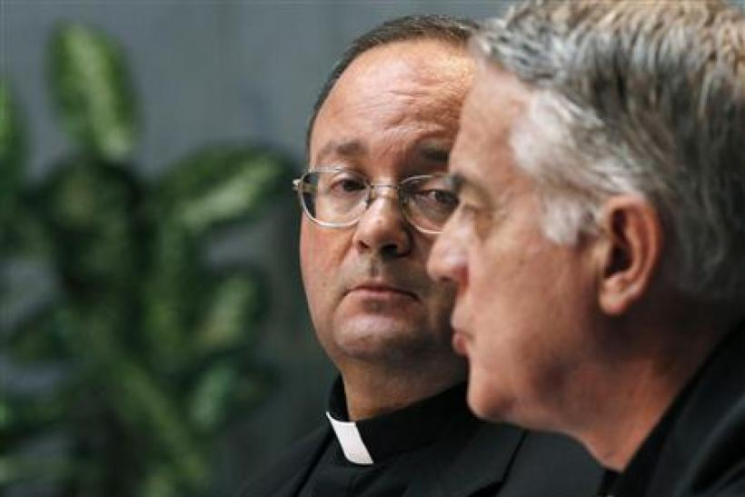 Monsignor Scicula, a Vatican doctrinal official, watches as Vatican's spokesman Father Lombardi speaks at the Vatican