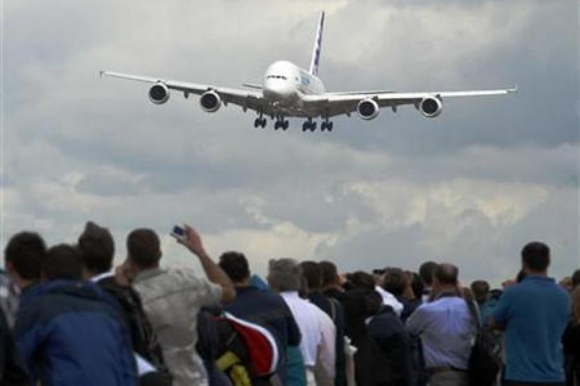 An Airbus A380 plane is watched by spectators as it lands at the Farnborough Airshow