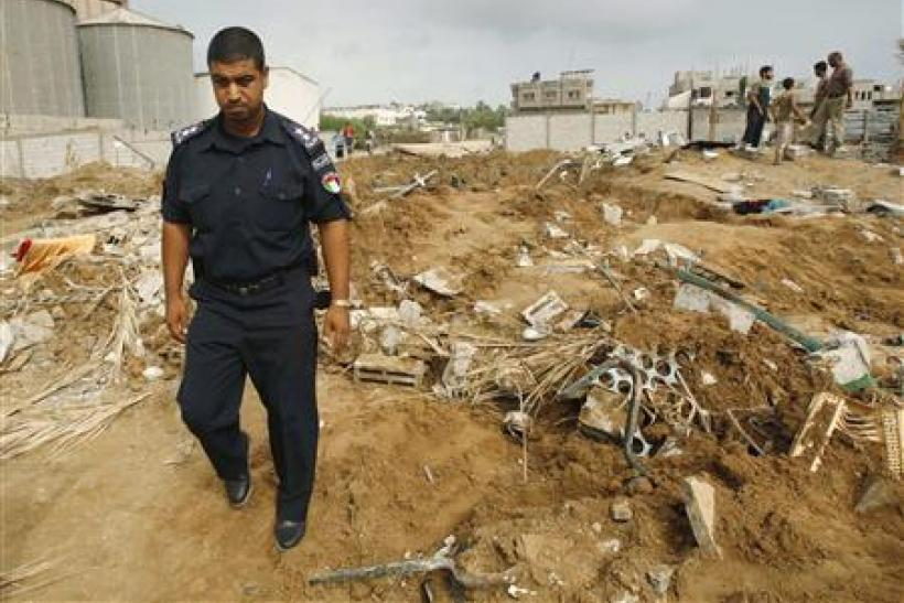 Hamas policeman surveys the damage after Israeli air strikes in the central of Gaza Strip