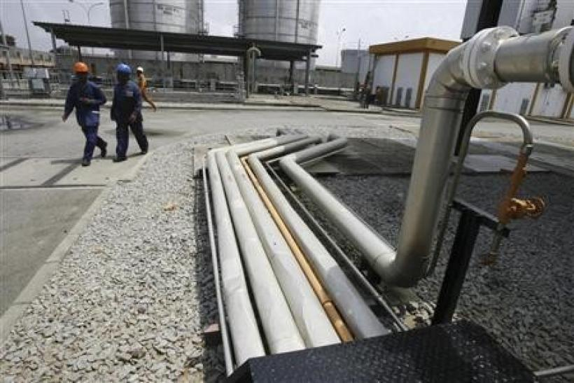 Workers walk past gas pipelines at Ivory coast Electricity Production Company (CIPREL) thermal power station in Abidjan