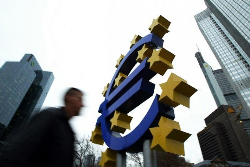 A pedestrian walks by a huge Euro logo in front of the European Central Bank (ECB) in Frankfurt