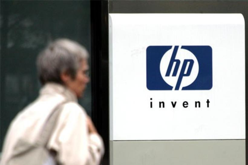 A woman walks past the Hewlett Packard logo