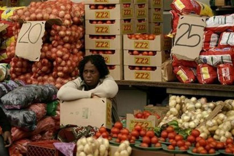A vegetable vendor sits next to her stall in Kliptown, Soweto