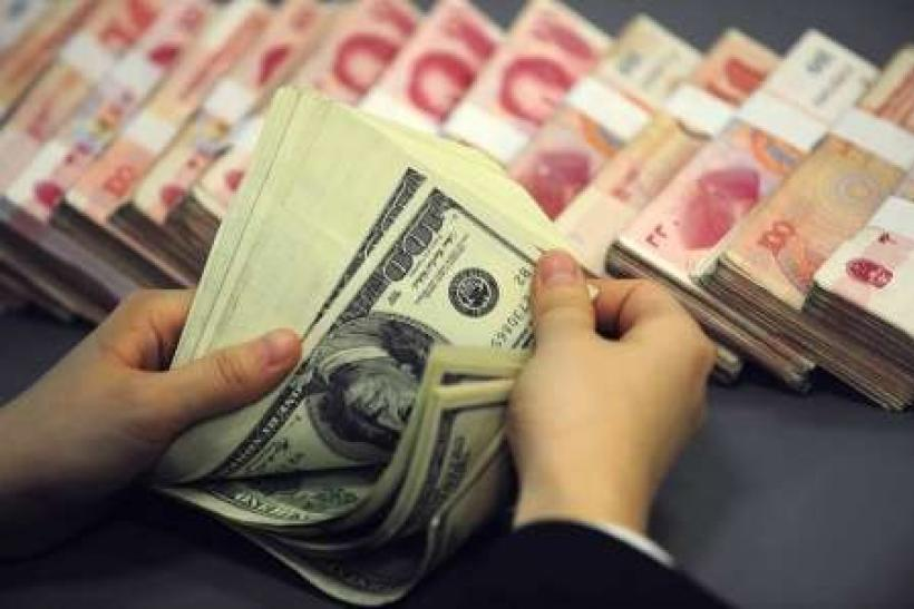 An employee counts U.S. currency near renminbi notes at a bank in Hefei, Anhui province