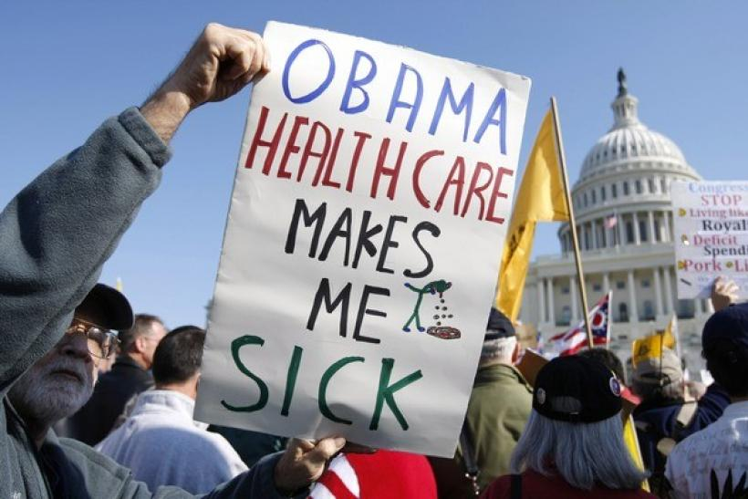 """A demonstrator holds up a sign during a """"House Call"""" rally against proposed healthcare reform legislation at the Capitol in Washington November 5, 2009."""