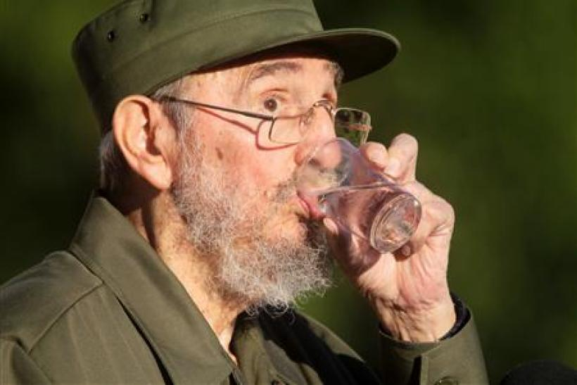Former Cuban leader Fidel Castro drinks water during a meeting with students at Havana's University