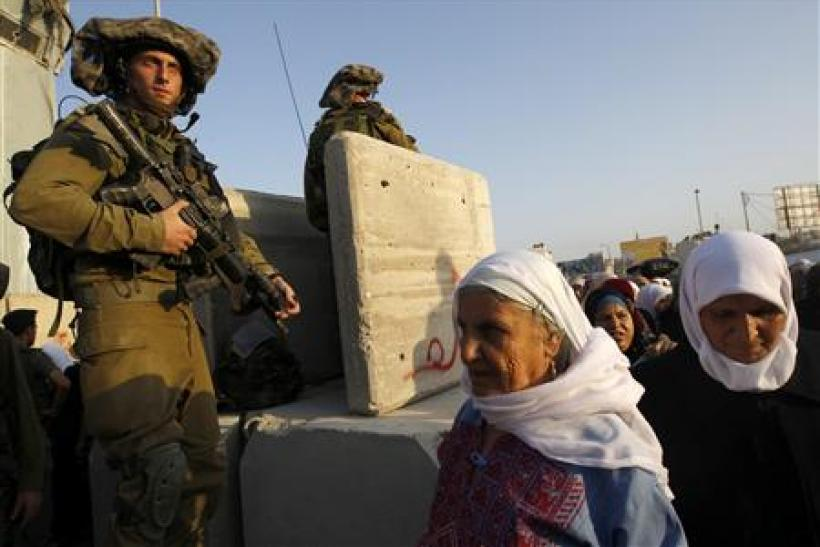 Palestinian women cross towards Jerusalem through Israel's Qalandiya checkpoint outside Ramallah