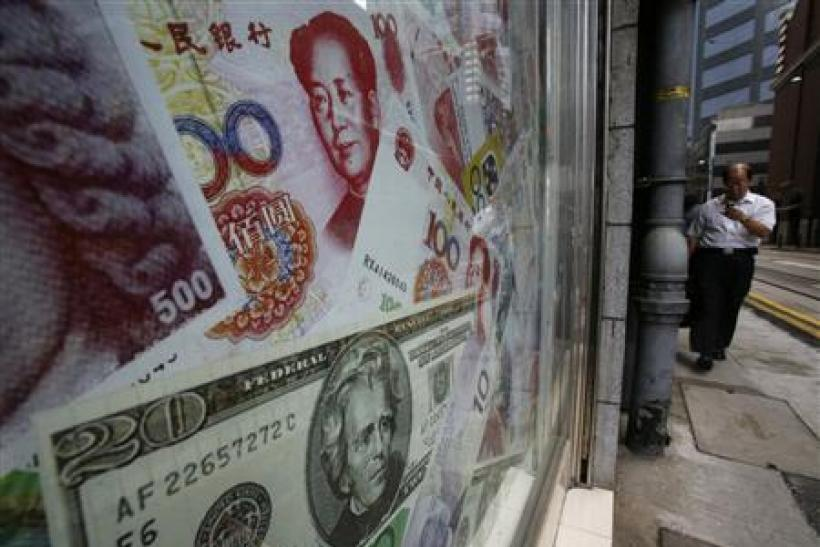 Photos of yuan and U.S. dollar banknotes are displayed at a money exchange in Hong Kong