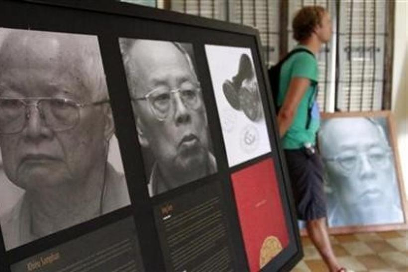 A tourist walks past portraits of former Khmer Rouge President Khieu Samphan (L), 78, and ex-Foreign Minister Ieng Sary, 84, at Toul Sleng genocide museum in Phnom Penh