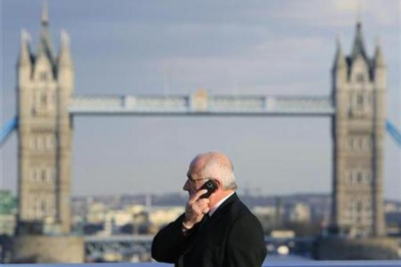 A man talks on a mobile telephone in front of Tower Bridge whilst walking across London Bridge in London
