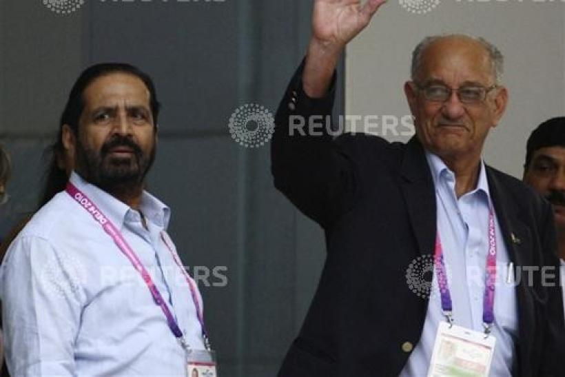 Michael Fennell, president of the Commonwealth Games Federation, waves upon his arrival as the President of the Indian Olympic Association (IOA) and Commonwealth Organising Committee Chairman Suresh Kalmadi watches at the airport in New Delhi September 23