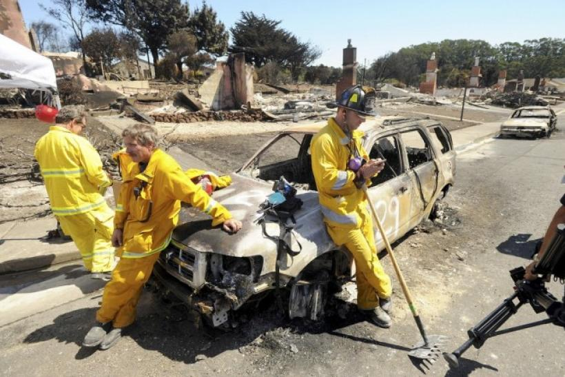 Emergency personnel lean against a burned out car at the site of a natural gas explosion in pipeline San Bruno, California September 11, 2010.