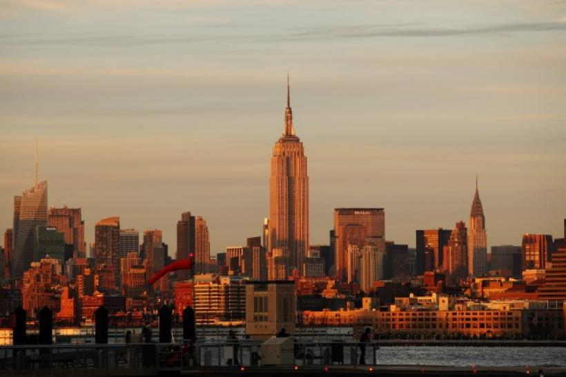 The Empire State Building sits between the Bank of America building and the Chrysler Building at sunset in New York