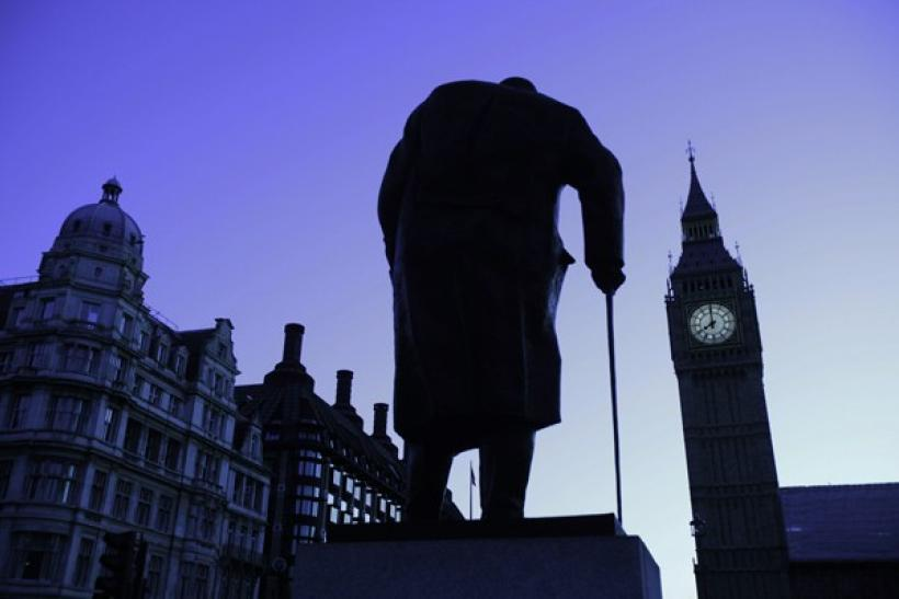 The Big Ben clock and a statue of former British Prime Minister Winston Churchill are silhouetted against the morning sky in central London