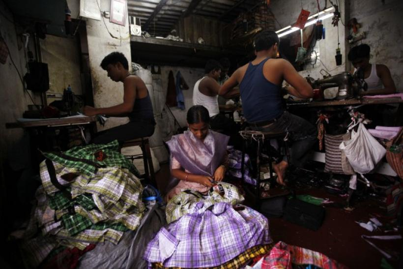 Fifteen-year-old Saira (C) cuts shirt threads inside a garment factory in Mumbai August 3, 2010.