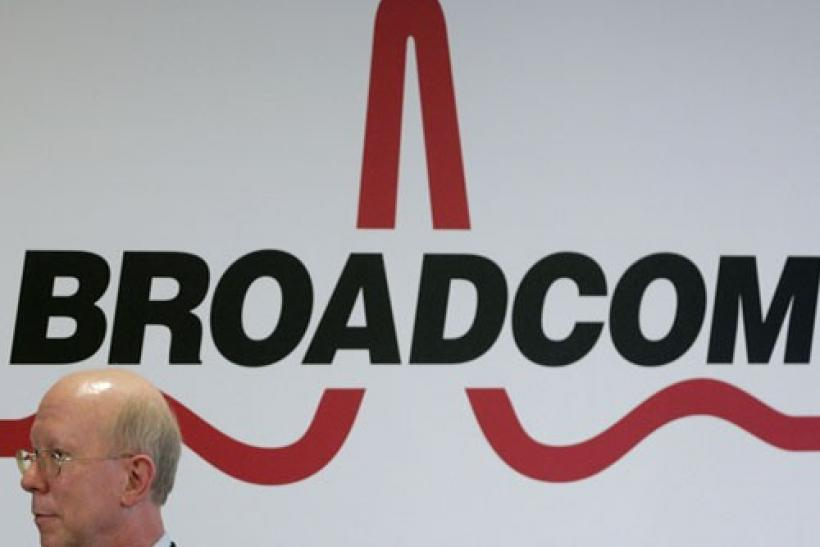 Broadcom CEO Scott McGregor stands in front of the company's logo in Taipei