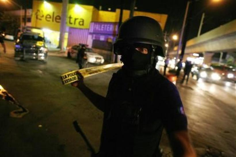 A policeman cordons off a crime scene where gunmen tried to kidnap a government official outside the Topo Chico prison, in a gruesome war between Mexico's powerful Gulf cartel and its former armed wing, the Zetas