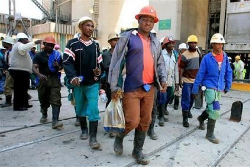Mine workers emerge from the pithead at the Harmony Gold mine in Carletonville, west of Johannesburg,