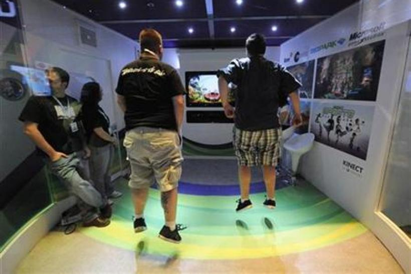 Attendees play Kinect Adventures for Microsoft Xbox in an enclosed booth at the E3 Media & Business Summit in Los Angeles
