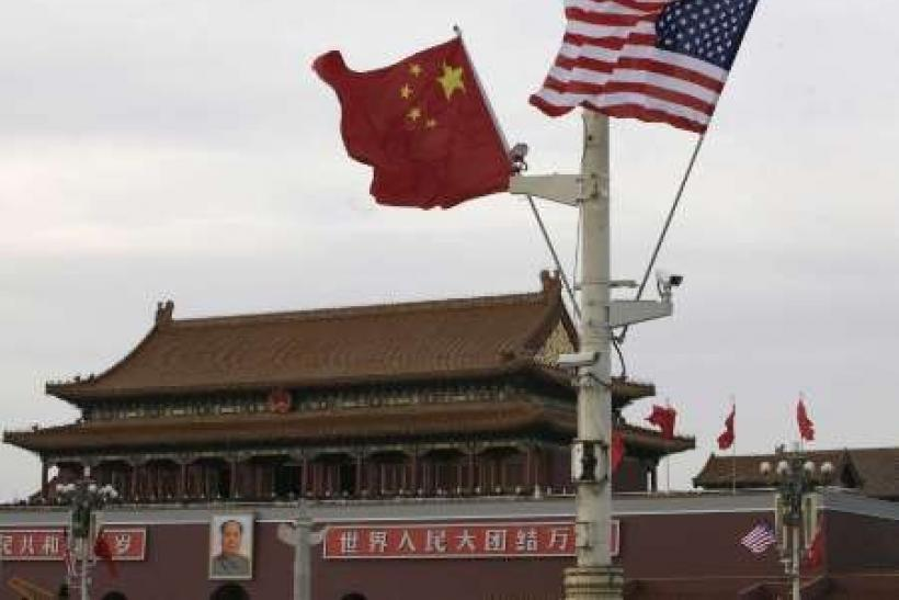 A U.S. and a Chinese flag flutter in front of Tiananmen Gate in Beijing