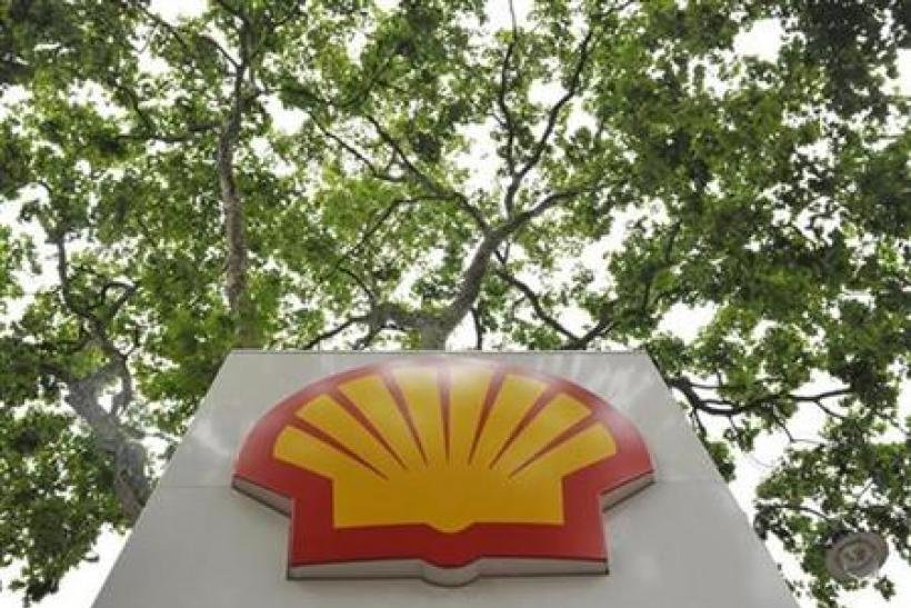 A logo is seen under a canopy of trees at a Shell gas station in central London