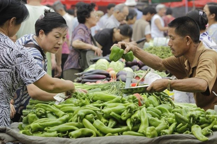 Customers select vegetables at a market in central Beijing, August 11, 2010.