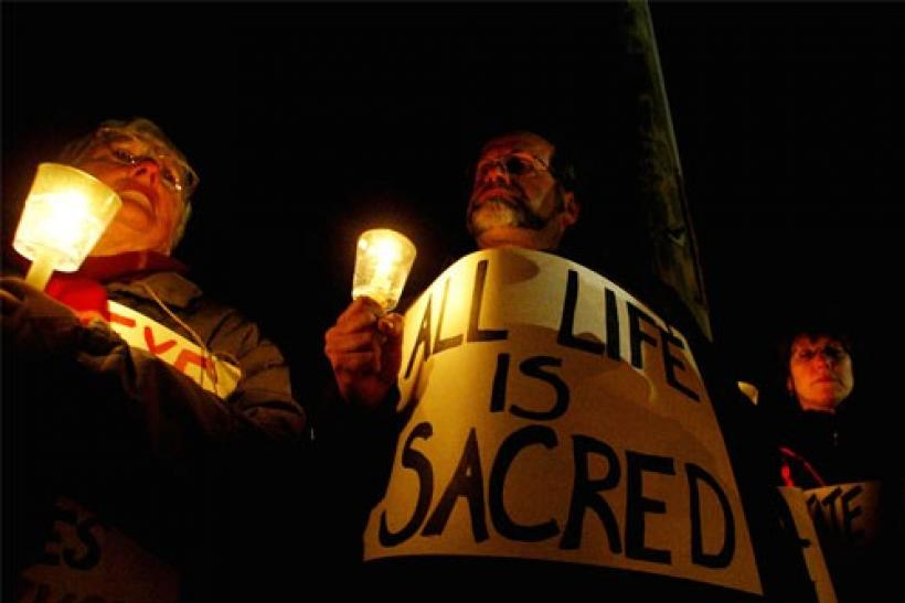 Protesters of death penalty hold candles during a vigil outside the gates to the Osborn Correctional Institution in Enfield, Connecticut, against the execution of serial killer Michael Ross, early May 13, 2005